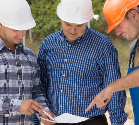 image of three male employees wearing construction hard hats looking at a diagram overjoyed with their new Bartlett TN Contactor's Insurance.