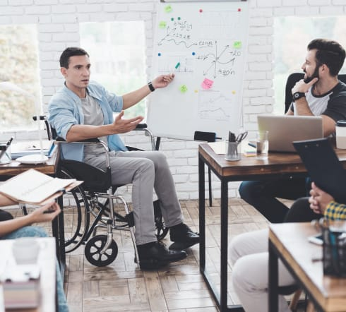 image of a man on a wheelchair pointing to a graph about Group Disability Insurance while two other man stare at what he's pointing at in a Bartlett TN office