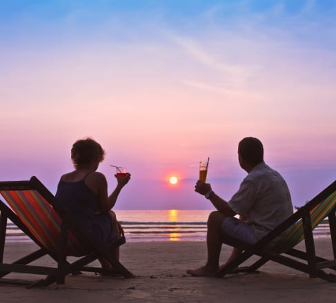 image of a couple sitting on the beach watching the sun set glad that they are covered by the best Retirement Insurance in Bartlett TN